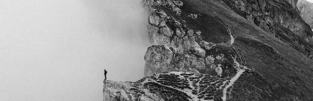 Man standing on edge of cliff in the fog